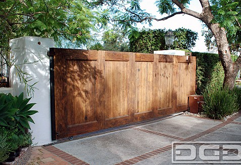 Custom designed spanish garage door matching automatic for Wooden sliding driveway gates